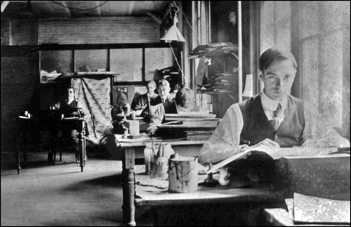 Tom Thomson as a graphic artist at Grip Limited; J.E.H. MacDonald seen in background at end of...jpg