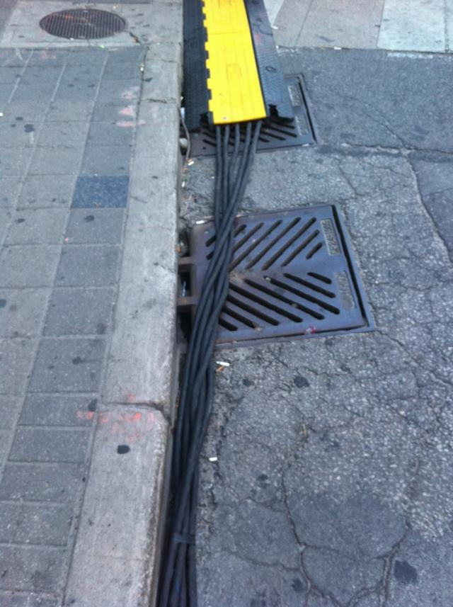 Wires lining street gutter with pedestrian covers.