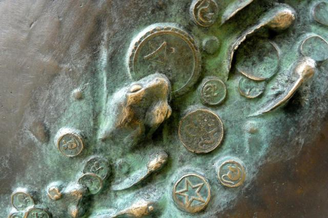 A frog emerges amongst polliwogs and ancient coins which populate the spiral gro
