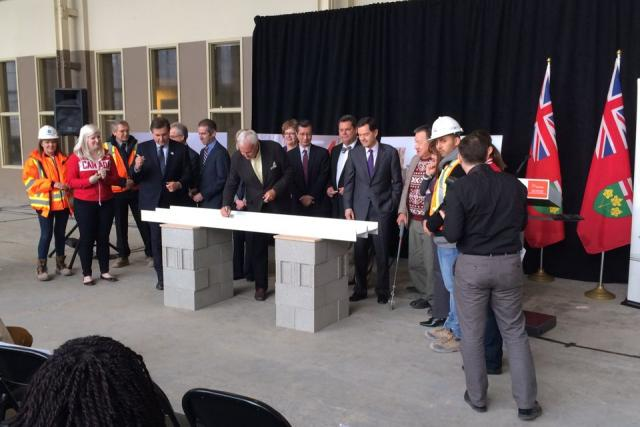 Dignitaries, with David Peterson at centre, gather to sign the last beams at the