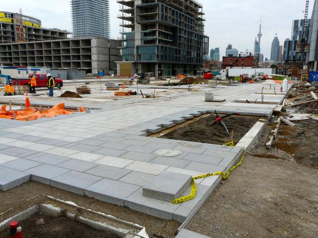 Pavers being laid for the Front Street Promenade in the Pan Am Village, Toronto