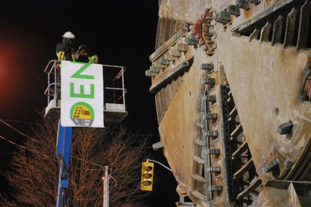 Workers place a 'Dennis' banner on south side of TBM, image by Marcus Mitanis