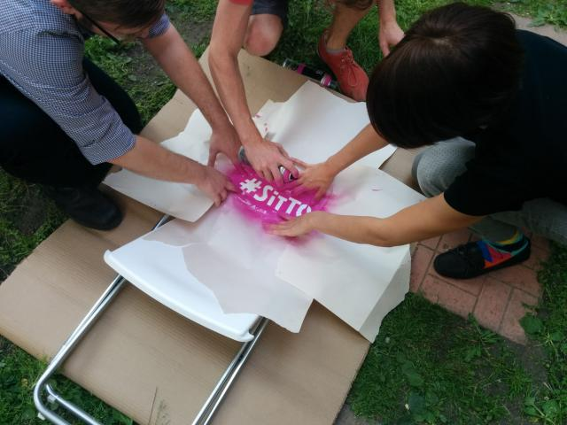 The #SitTo tag being applied to a chair, image courtesy of Fabienne Chen / #SitT