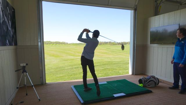 Elliot Isenor watches a swing at the Fox Harb'r Golf Academy, Nova Scotia