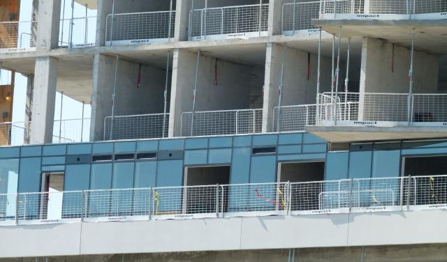 Detail view of the curtain wall cladding being installed at Aqualina