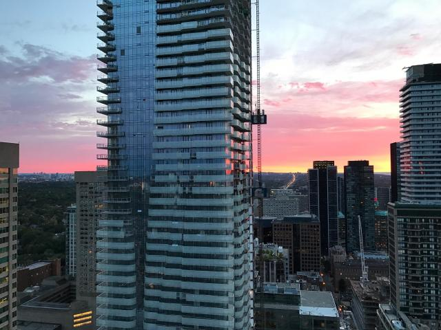 Sunrise view of balcony glass installation at One Bloor East, image by Benito