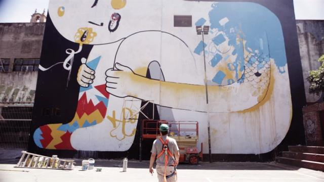 A muralist considers his work in White Walls Say Nothing, image courtesy of hotd