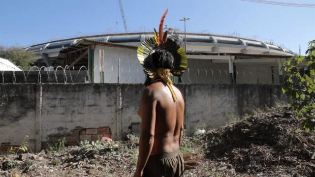 An indigenous Brazilian looks over at Maracaña Stadium in State of Exception, im